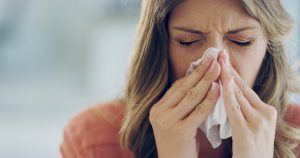 Office worker sneezing into a tissue